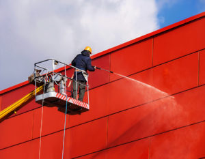 Worker Of Professional Facade Cleaning Services Washing The Red